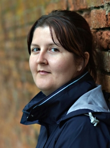 A photo of volunteer Leigh Yeates, wearing a blue coat and leaning against a brick wall in three quarter profile.