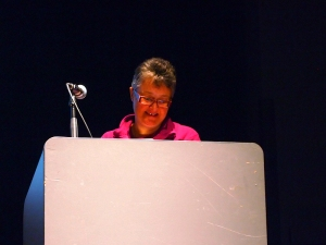 Close up photo of speaker chris sherlock delivering her talk from the podium on the stage
